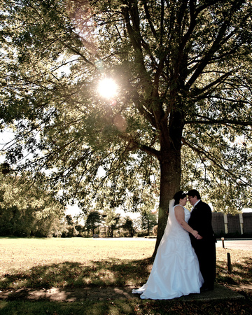 Bride and Groom Standing by tree