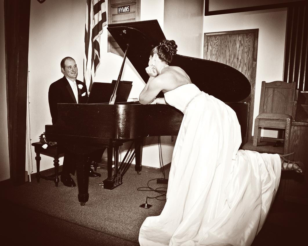 bride watching groom play piano