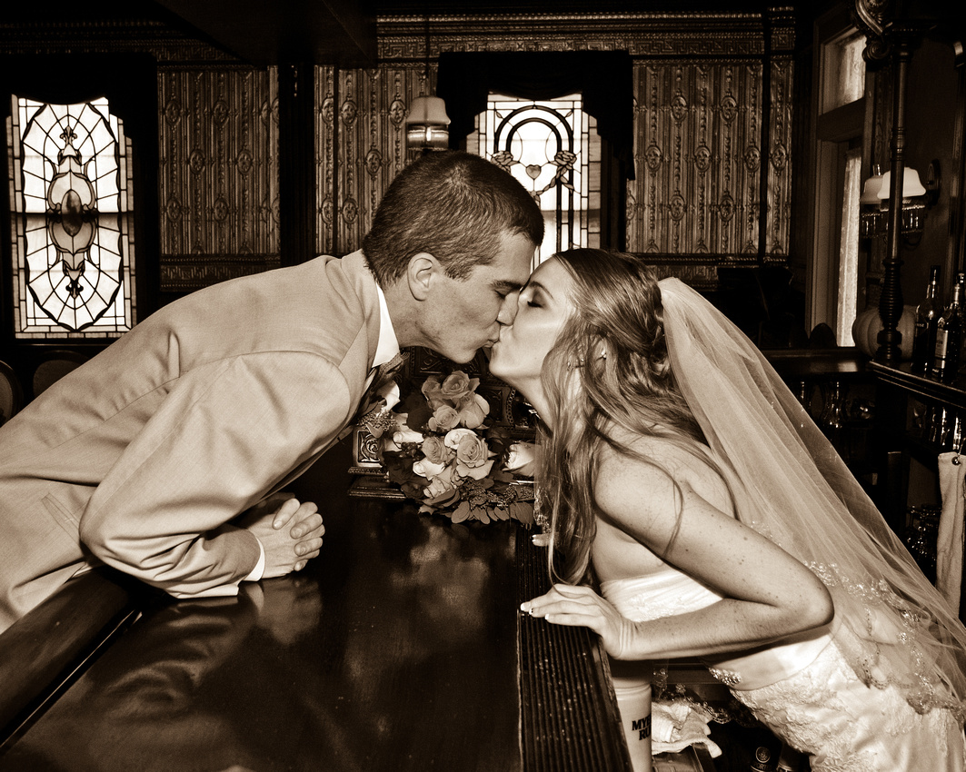 Bride and groom kissing over bar